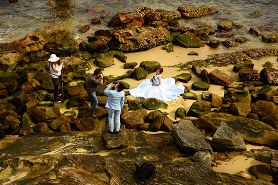 A bride getting photographed on the sand and rocks at low tide at Bradleys Head, Sydney