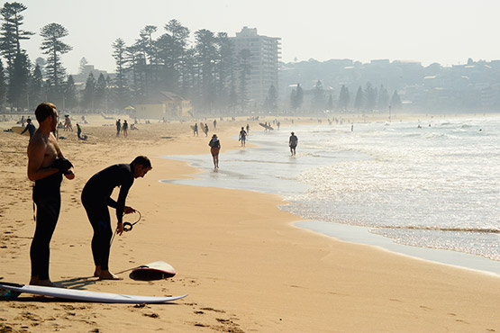 Two men prepare for a morning of surfing at Manly Beach, Sydney