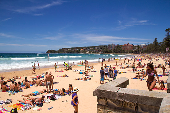 Manly Beach is buzzing with beach-goers on a warm Sydney day