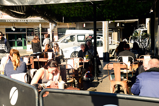 An outdoor cafe at the junction of King Street and Enmore Road marks the centre of the Newtown shopping strip.