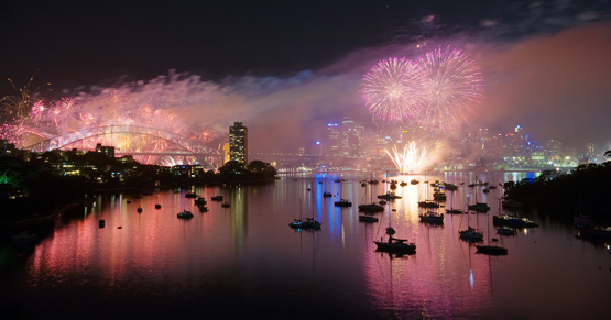 Sydney Harbour is clothed in a purple mist by New Year's Eve fireworks